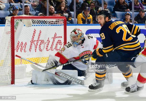 Harri Sateri of the Florida Panthers makes a save as Zemgus Girgensons of the Buffalo Sabres looks for the puck during the second period of an NHL...