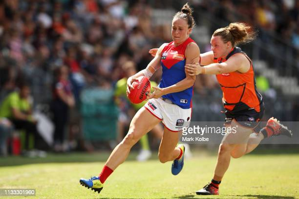 Harriet Cordner of the Demons kicks under pressure from Louise Stephenson of the Giants during the round five AFLW match between the Greater Western...
