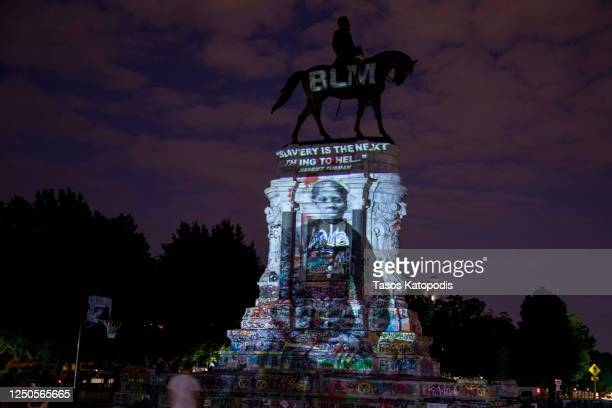 Harriet Tubman's image is projected on the Robert E. Lee Monument as people gather around on June 18, 2020 in Richmond, Virginia. Richmond Circuit...