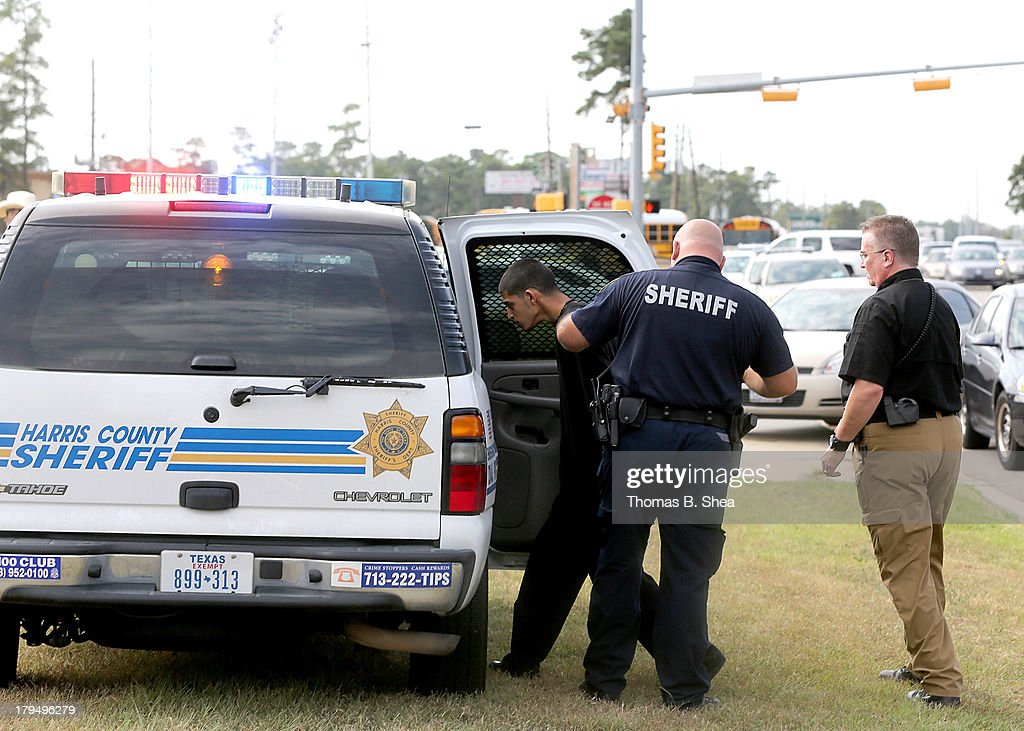 A Harris County Sheriff takes a person into custody on the grounds of Spring High School September 4, 2013 in Spring, Texas. A 17-year-old student was fatally stabbed and three other students during what has been reported as a fight at the school about 7:00 am. Three people have been taken into custody.