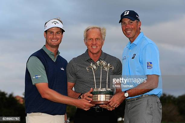 Harris English and his teammate Matt Kuchar pose with the the tournament trophy and host Greg Norman following their victory after the final round of...