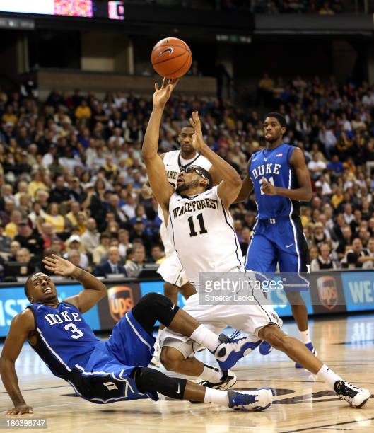 Harris of the Wake Forest Demon Deacons runs into Tyler Thornton of the Duke Blue Devils as he drives to the basket during their game at Lawrence...