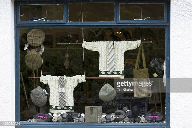 Harris tweed and traditional tartan items on display for sale in shop window of gift and souvenir shop on Isle of Iona in Scotland