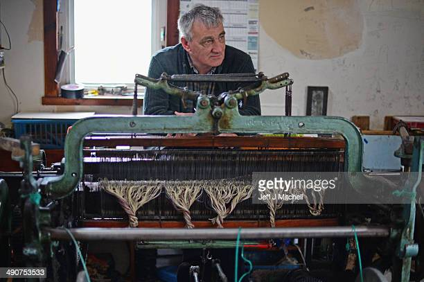 Harris tweed weaver Donald John Mackay sits behind his Hattersely single width loom in his shed in the village of Luskentyre May 14,2014 in Harris,...