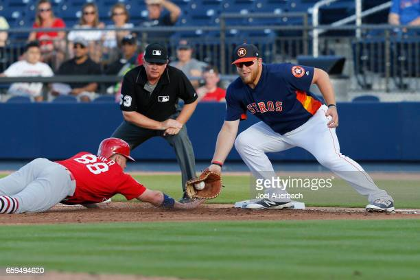Harrison Bader of the St Louis Cardinals gets back safe under the tag by AJ Reed of the Houston Astros in the first inning during a spring training...