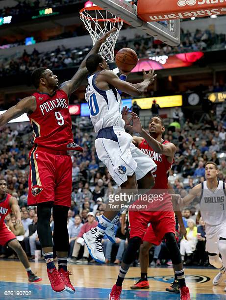 Harrison Barnes of the Dallas Mavericks drives to the basket against Terrence Jones of the New Orleans Pelicans and Alexis Ajinca of the New Orleans...