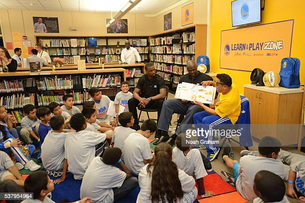 Harrison Barnes of the Golden State Warriors and former player Adonal Foyle reads a book with the children at the 2016 NBA Finals Cares Legacy...
