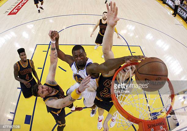 Harrison Barnes of the Golden State Warriors dunks against Timofey Mozgov and Mike Miller of the Cleveland Cavaliers in the second half during Game...