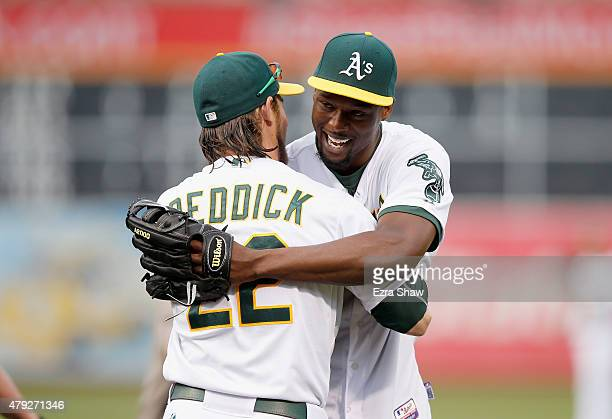 Harrison Barnes of the Golden State Warriors hugs Josh Reddick of the Oakland Athletics after he threw out the ceremonial first pitch before the...
