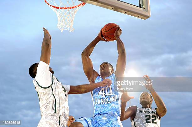 Harrison Barnes of the North Carolina Tar Heels goes up for a shot against Derrick Nix and Branden Dawson of the Michigan State Spartans in the first...
