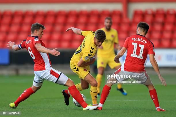 Harrison Biggins of Fleetwood battles with James Jones of Crewe and Callum Ainley of Crewe during the Carabao Cup First Round match between Crewe...