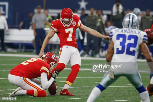 Harrison Butker of the Kansas City Chiefs kicks a field goal as Dustin Colquitt of the Kansas City Chiefs holds in the first half of a football game...