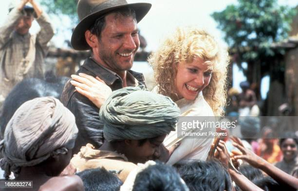 Harrison Ford and Kate Capshaw are greeted by children in a scene from the film 'Indiana Jones And The Temple Of Doom' 1984