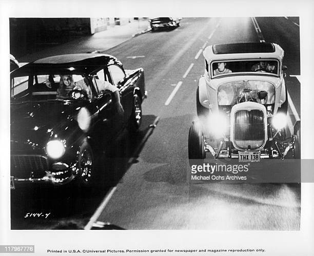 Harrison Ford in a 1955 Chevy with his hand hanging out of the car window and Paul Le Mat in a 1932 Ford coupe in a scene from the film 'American...