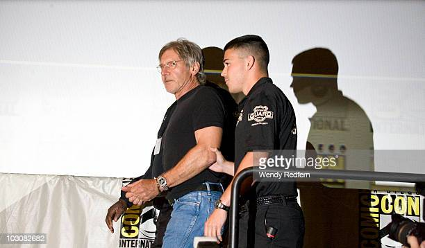 Harrison Ford is escorted by security after speaking at the Cowboys and Aliens panel at ComicCon on July 24 2010 in San Diego California