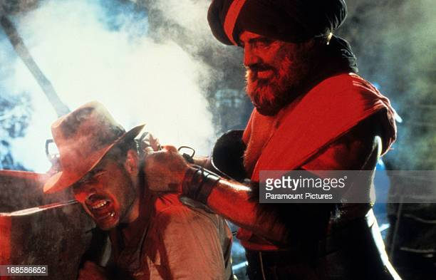 Harrison Ford is threatened with a knife in a scene from the film 'Indiana Jones And The Temple Of Doom' 1984