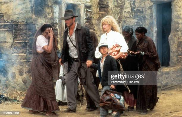 Harrison Ford Jonathan Ke Quan and Kate Capshaw are lead through a temple in a scene from the film 'Indiana Jones And The Temple Of Doom' 1984