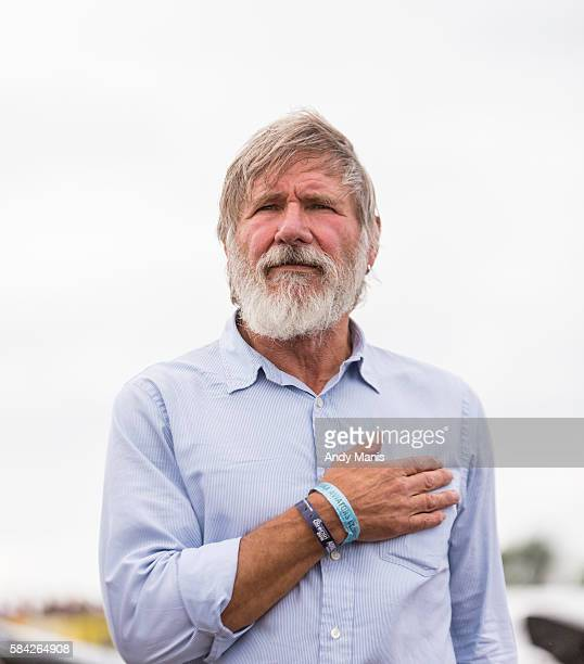 Harrison Ford places his hand over his heart during the playing of the 'StarSpangled Banner' at the EAA's AirVenture Air Show on July 28 2016 in...