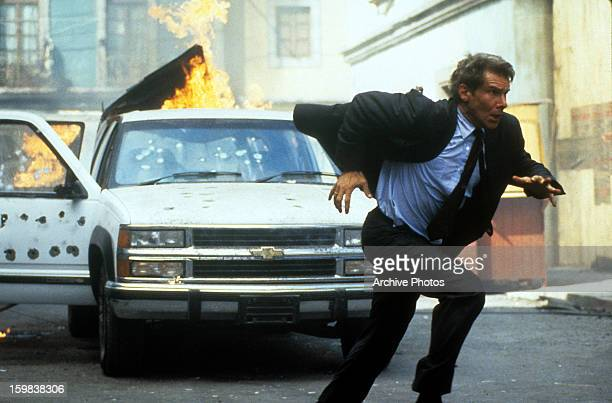 Harrison Ford running from a burning car and bullet shots in a scene from the film 'Clear and Present Danger' 1994