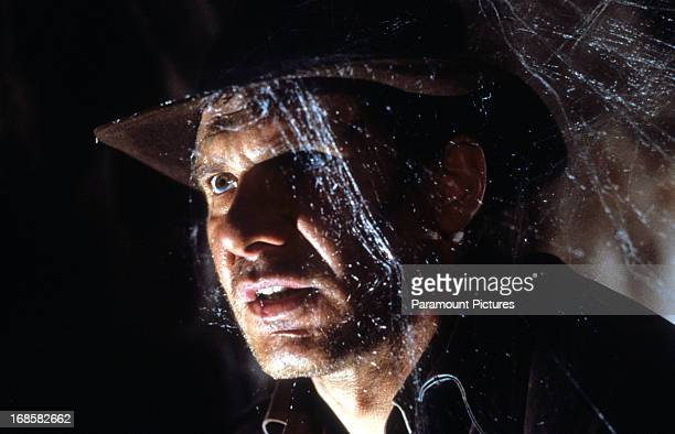 Harrison Ford walks through cobwebs in a scene from the film 'Indiana Jones And The Last Crusade' 1989