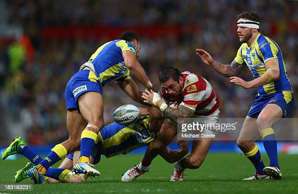 Harrison Hansen of Wigan Warriors loses the ball under pressure from Richard Myler and Ryan Atkins of Warrington Wolvesduring the Super League Grand...