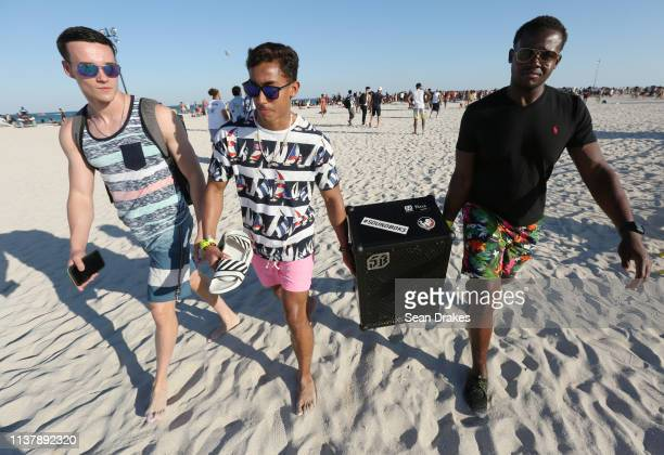 Harrison Holmes Angel Soto and Odysson Riley students of Florida State University carry a portable speaker system to provide music for beachgoers...