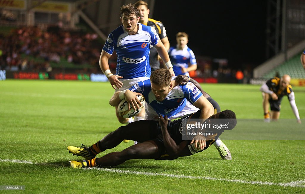 Harrison Keddie of Newport Gwent Dragons dives over Christian Wade to score the match winning try in the final against Wasps during the Singha Premiership Rugby 7's Series finals at Twickenham Stoop on August 28, 2015 in London, England.