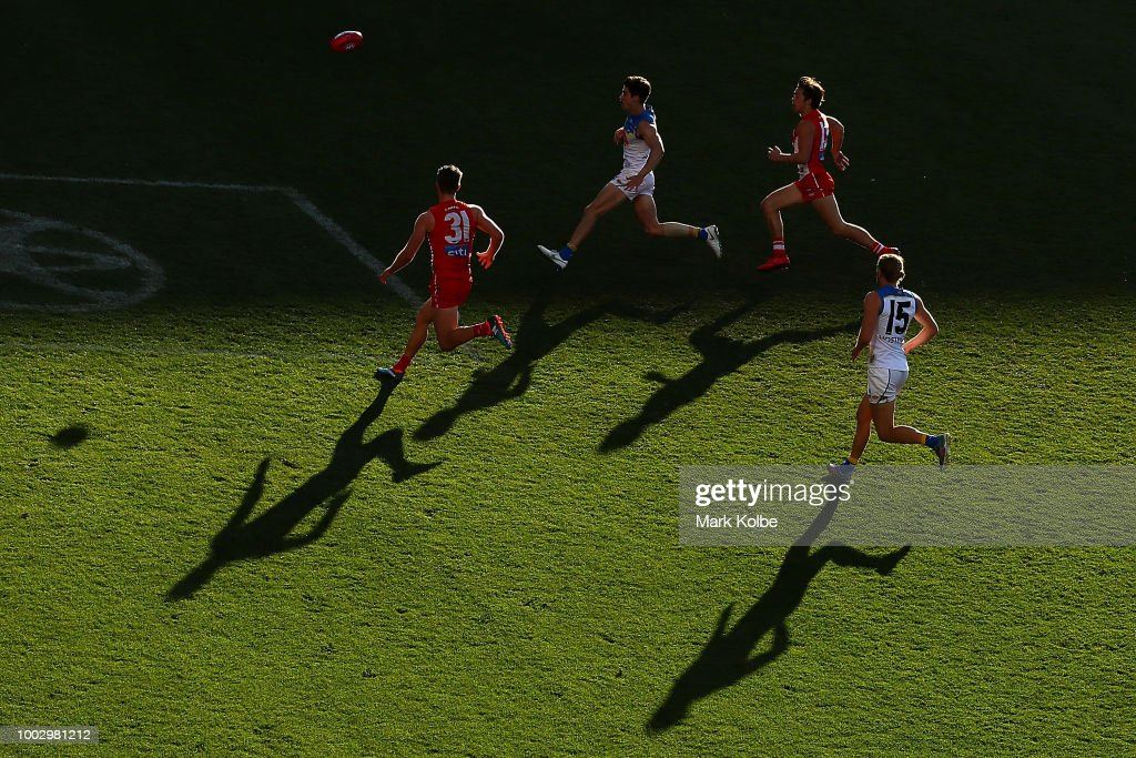 Harrison Marsh of the Swans, Alex Sexton of the Suns, Oliver Florent of the Swans and Aaron Young of the Suns chase the ball during the round 18 AFL match between the Sydney Swans and the Gold Coast Suns at Sydney Cricket Ground on July 21, 2018 in Sydney, Australia.