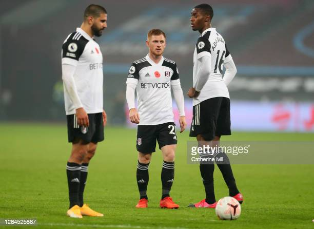 Harrison Reed of Fulham stands with Tosin Adarabioyo and Aleksandar Mitrovic of Fulham during the Premier League match between West Ham United and...
