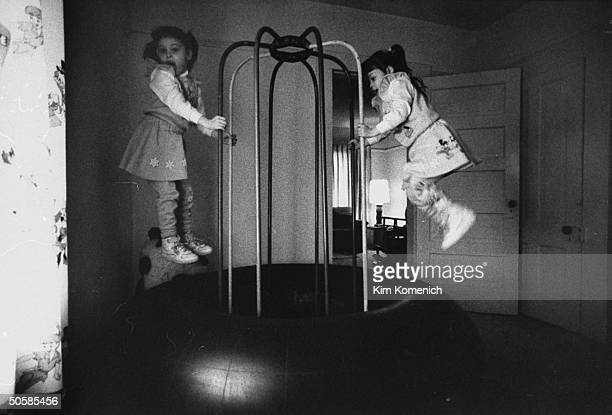 Harrison sisters Jaime Sherry jumping on huge inflated inner tube w steel handle bars in darkened playroom at home they are victims of a potentially...