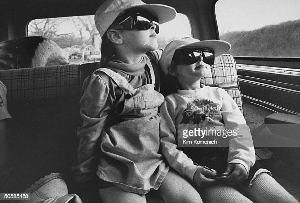 Harrison sisters Jaime Sherry wearing baseball caps sunglasses for protection against ultraviolet light as they sit in car on their way to the dr the...