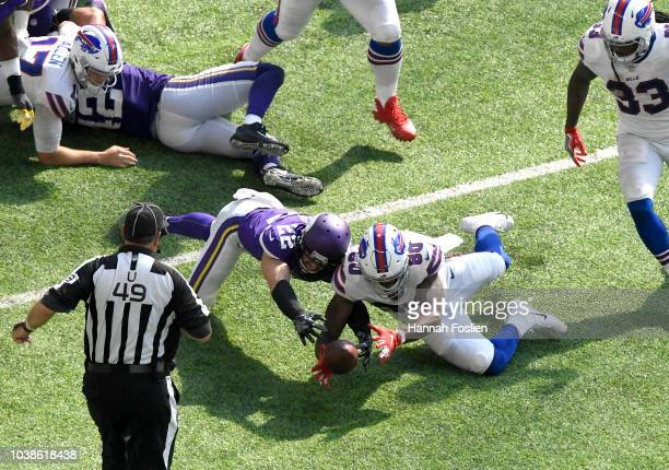Harrison Smith of the Minnesota Vikings and Jason Croom of the Buffalo Bills dive for a loose ball after it was fumbled by Josh Allen in the third...