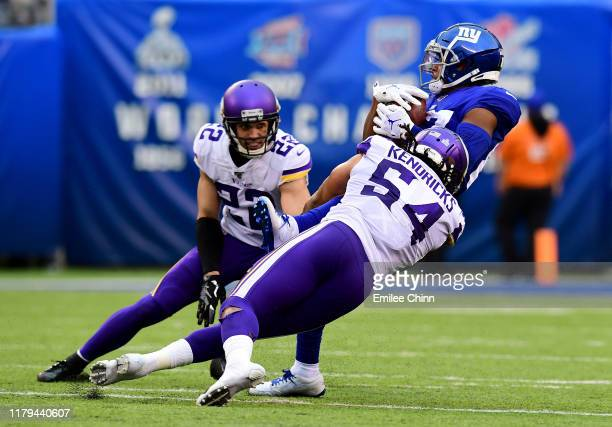 Harrison Smith watches as teammate Eric Kendricks of the Minnesota Vikings tackles Sterling Shepard of the New York Giants during their game at...