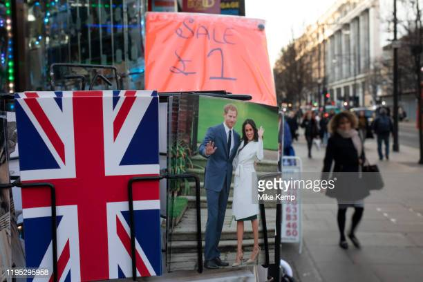 Harry and Meghan postcards for sale next to a Union Jack flag card as if they are waving goodbye to the UK on a rack on 21st January 2020 in London...