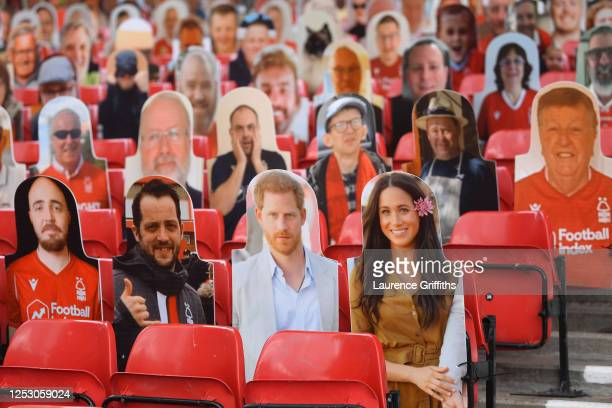 Harry and Meghan the Duke and Duchess of Sussex look out amongst the cardboard fans profile pictures in the main stand ahead of the Sky Bet...