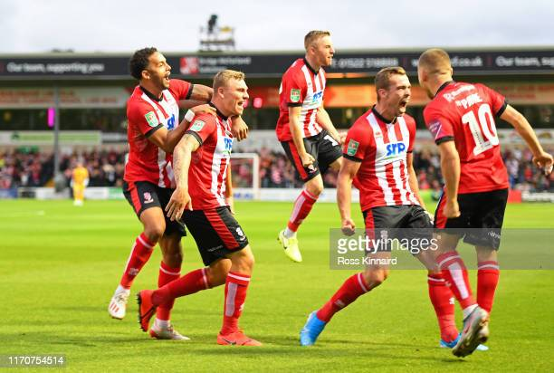 Harry Anderson of Lincoln City celebrates with team mates after scoring his team's first goal during the Carabao Cup Second Round match between...