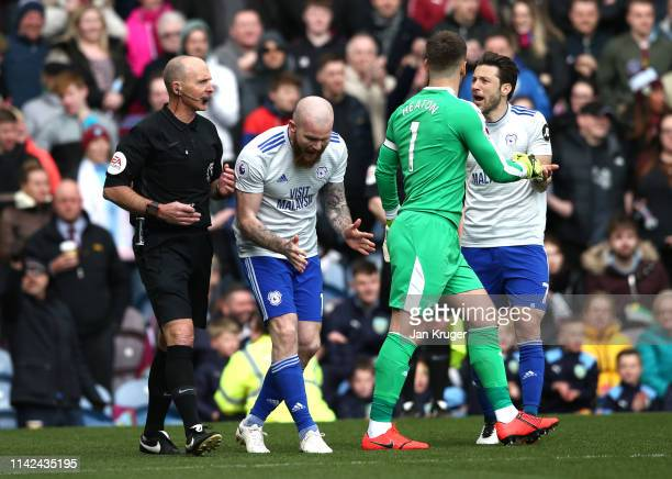 Harry Arter of Cardiff City argues with referee Mike Dean as Aron Gunnarsson of Cardiff City reacts during the Premier League match between Burnley...