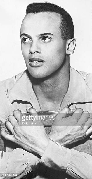 Harry Belafonte actorsinger is shown seated with his hands crossed in this publicity handout