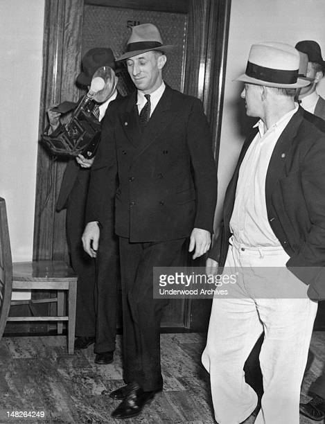 Harry Bridges militant leader of San Francisco's longshoremen leaves a conference with his bodyguard after a waterfront peace pact was signed ending...