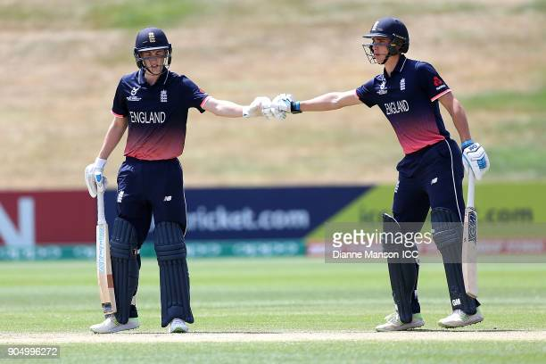 Harry Brook celebrates his half century with Will Jacks of England during the ICC U19 Cricket World Cup match between England and Namibia at John...
