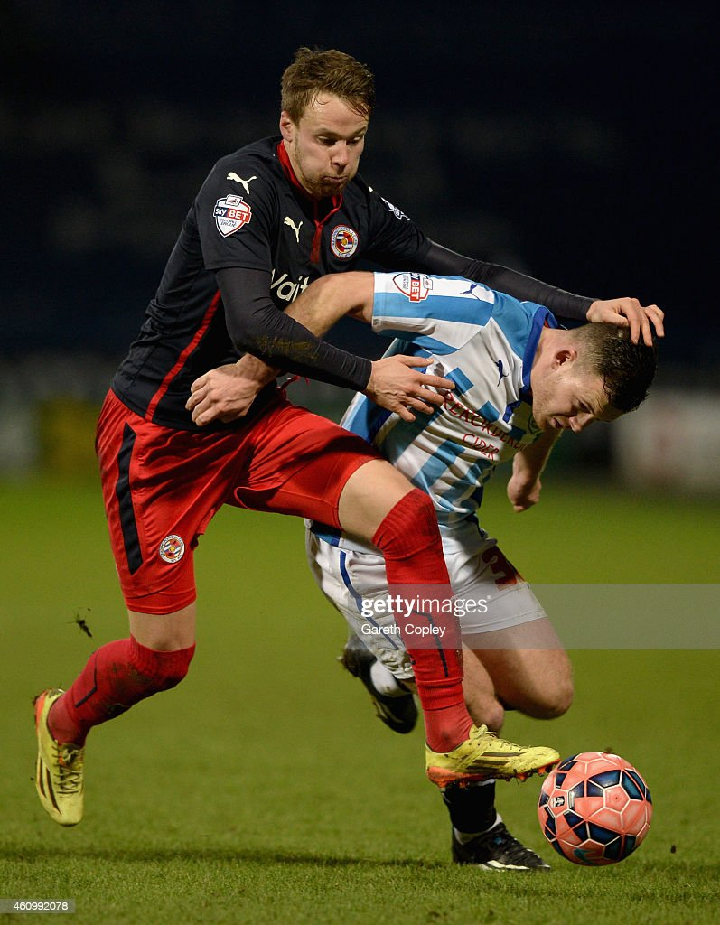 Harry Bunn of Huddersfield is tackled by Chris Gunter of Reading during the FA Cup Third Round match between Huddersfield Town and Reading at Galpharm Stadium on January 3, 2015 in Huddersfield, England.