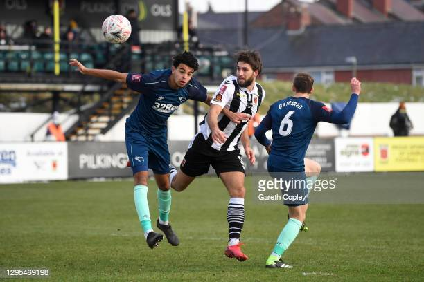 Harry Cardwell of Chorley FC battles for possession with Harrison Solomon and Joseph Bateman of Derby County during the FA Cup Third Round match...