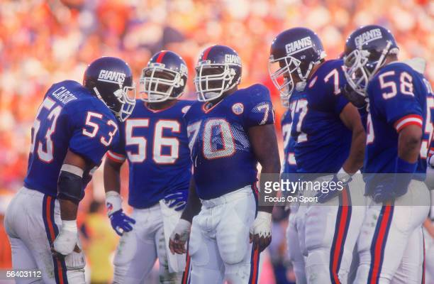 Harry Carson of the New York Giants talks with his teammates on the field during Super Bowl XXI against the Denver Broncos on January 25 1987 at the...