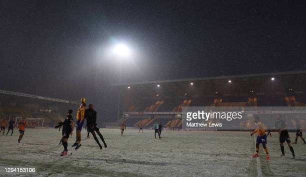 Harry Charsley of Mansfield Town and Cristian Montano of Port Vale challenge for the ball during the Sky Bet League Two match between Mansfield Town...
