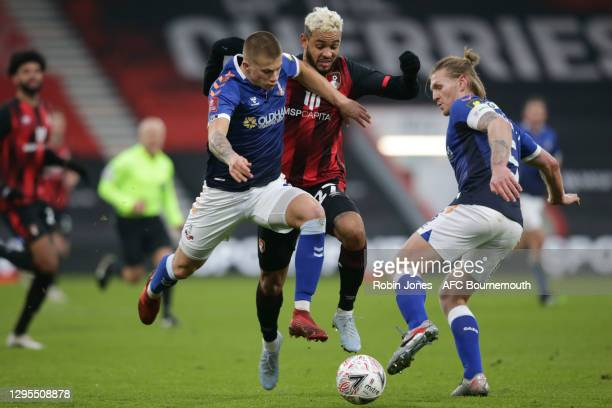 Harry Clarke and Carl Piergianni of Oldham Athletic hold up Joshua King of Bournemouth during FA Cup 3rd Round match between Oldham Athletic and AFC...