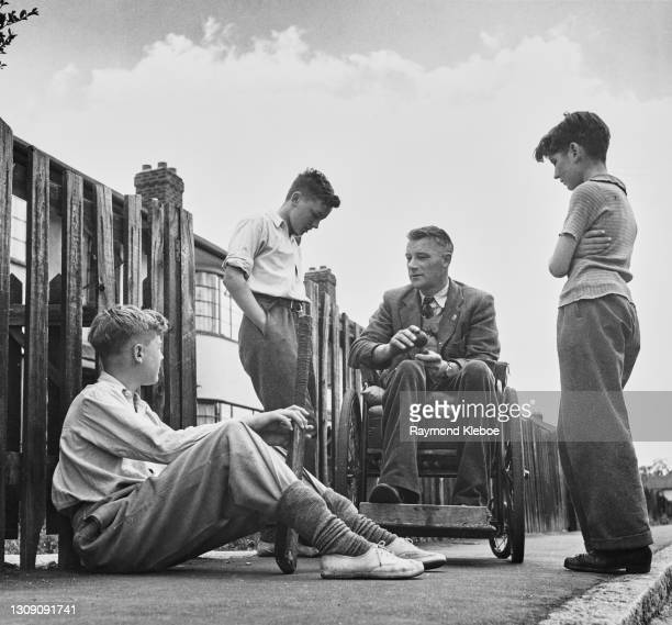 Harry Collier, a disabled ex-serviceman and former centre-forward for Westbury United, talking to a group of boys about football, August 1949....