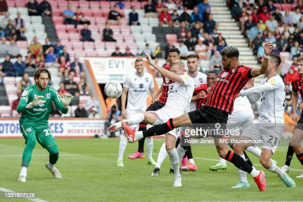 Harry Darling of MK Dons clears from Dominic Solanke of Bournemouth during the Carabao Cup 1st Round match between AFC Bournemouth and MK Dons at...