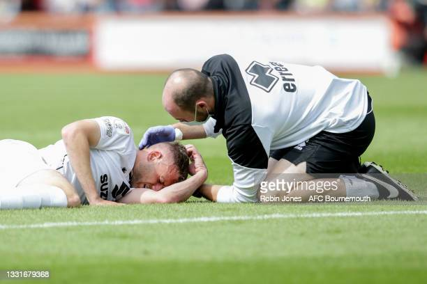 Harry Darling of MK Dons receieves treatment after a head collision with Emiliano Marcondes of Bournemouth during the Carabao Cup 1st Round match...