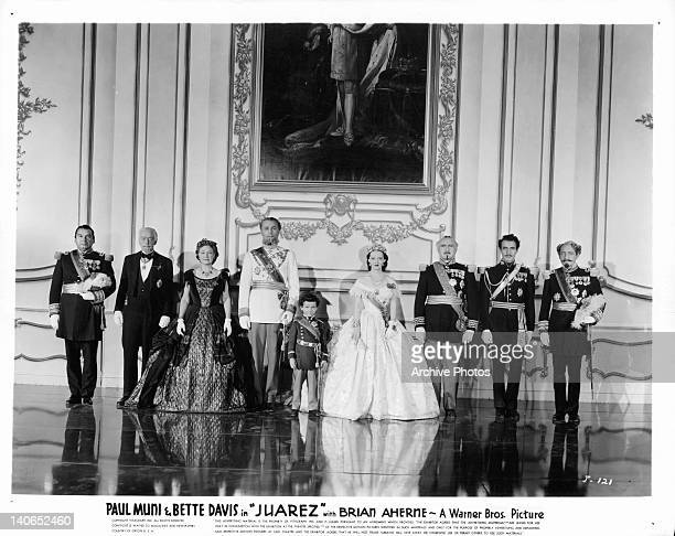 Harry Davenport, Brian Aherne, Bette Davis, Donald Crisp, Gilbert Roland and others standing before large portrait on the wall in a scene from the...