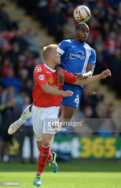 Harry Davis of Crewe Alexander challenges Tyrone Barnett of Peterborough United during their Sky Bet League One match at the Alexandra Stadium on...